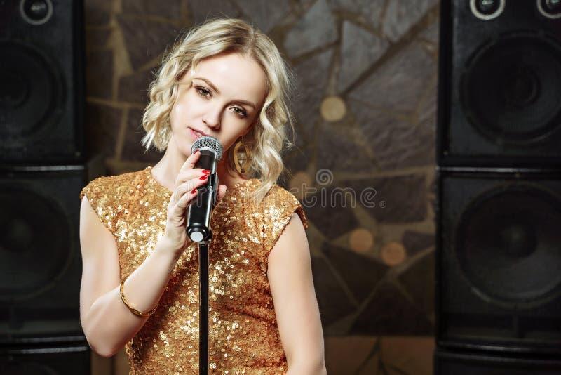 Portret van jonge blondevrouw met microfoon op donkere achtergrond stock afbeelding