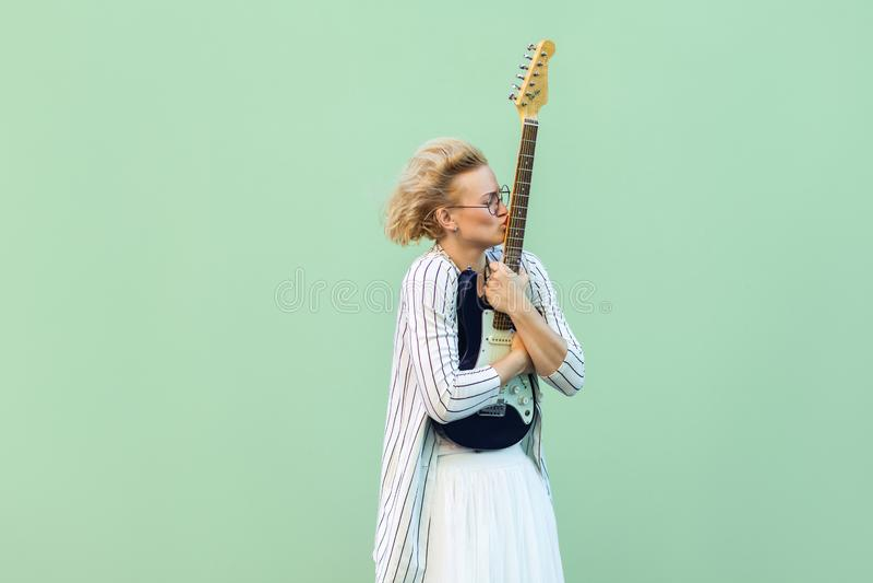 Portret van jonge blondevrouw in wit overhemd, rok, en gestreepte blouse met oogglazen die, en mooi haar bevinden zich houden kus stock afbeeldingen