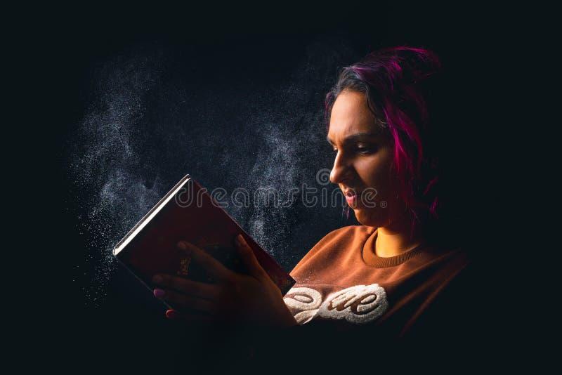 Portret van jonge boze vrouw die een stoffig boek op zwarte rustige achtergrond meppen stock foto