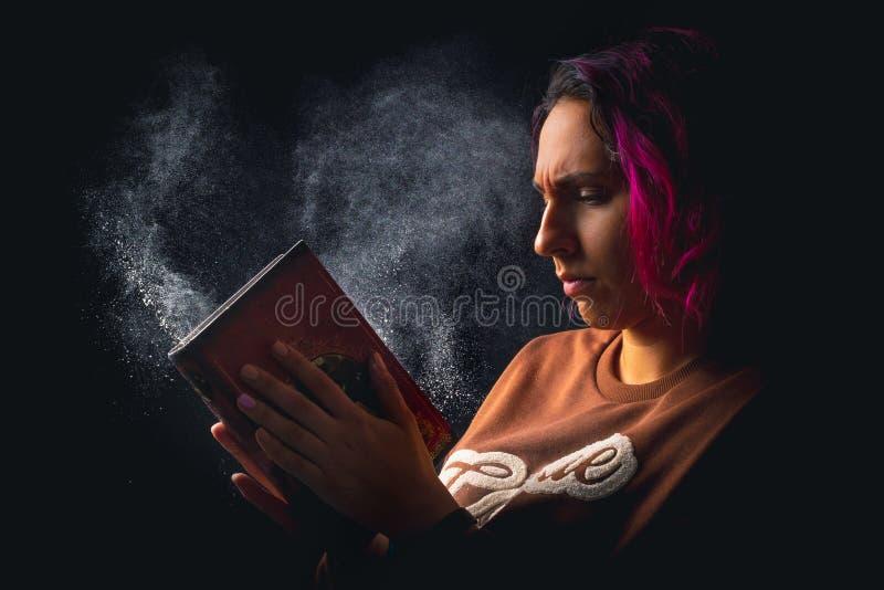 Portret van jonge boze vrouw die een stoffig boek op zwarte rustige achtergrond meppen royalty-vrije stock foto