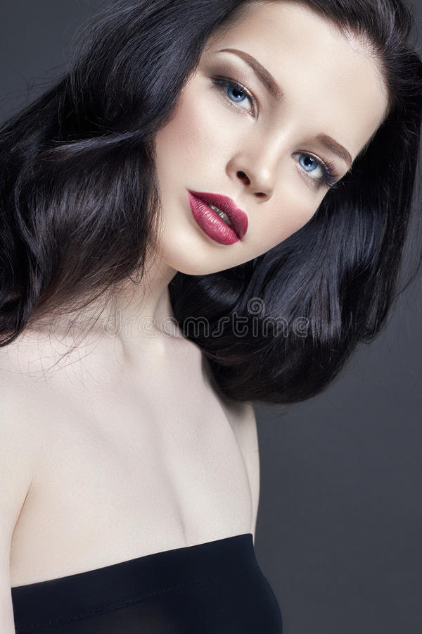 Portret van jonge donkerbruine vrouw tegen een donkere achtergrond Geheimzinnig helder beeld van vrouw met professionele make-up  stock afbeelding