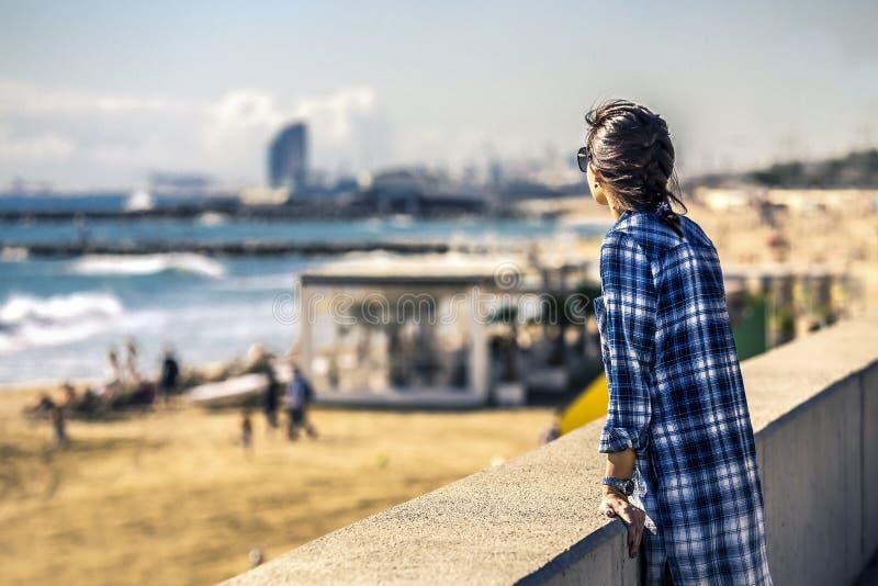 Portret van jonge en modieuze vrouw status op sea-front naast het zandige strand stock afbeeldingen
