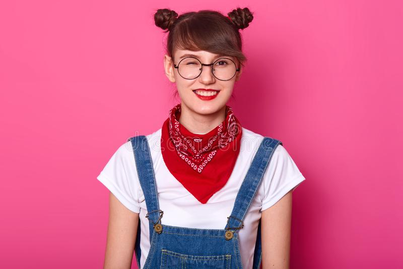 Portret van jonge energieke positieve vrolijke meisje status geïsoleerd over roze achtergrond in studio, die één gesloten oog hee stock afbeelding