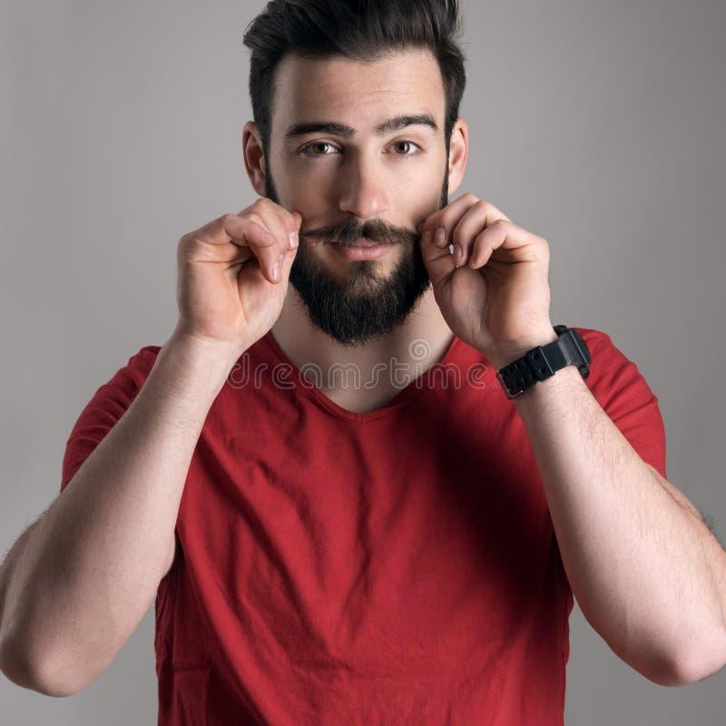 Portret van jonge expressieve hipster het aanpassen snor met vingers royalty-vrije stock foto