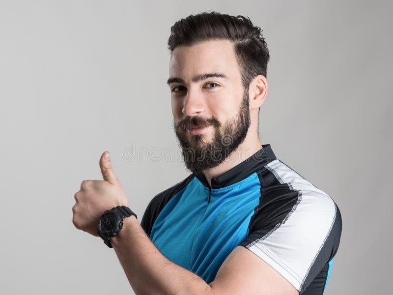 Portret van jonge fietser die het blauwe overhemd dragen die van fietserjersey duim op gebaar tonen royalty-vrije stock afbeeldingen