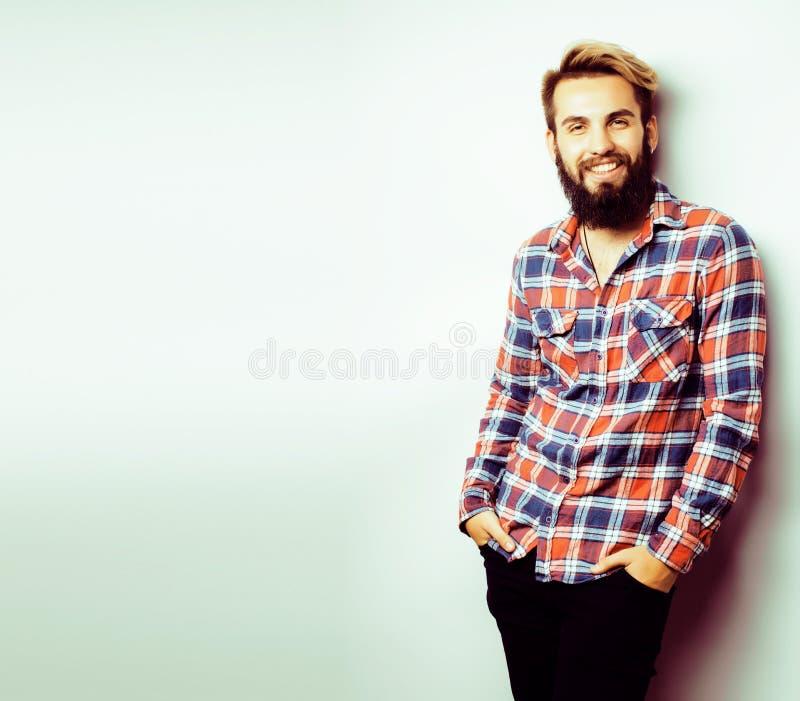 Portret van jonge gebaarde hipsterkerel die op witte achtergrond glimlacht stock afbeelding