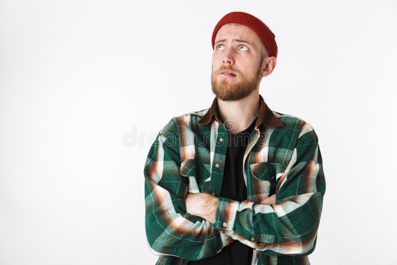 Portret van jonge gebaarde kerel die hoed en plaidoverhemd dragen die, terwijl status geïsoleerd over witte achtergrond omhoog er stock fotografie