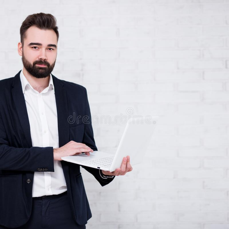 Portret van jonge gebaarde zakenman die computer over witte bakstenen muurachtergrond met behulp van royalty-vrije stock fotografie