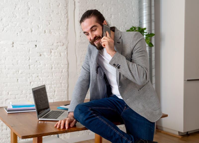 Portret van jonge gelukkige aantrekkelijke sprekende zaken van de ondernemersmens op mobiel stock afbeeldingen