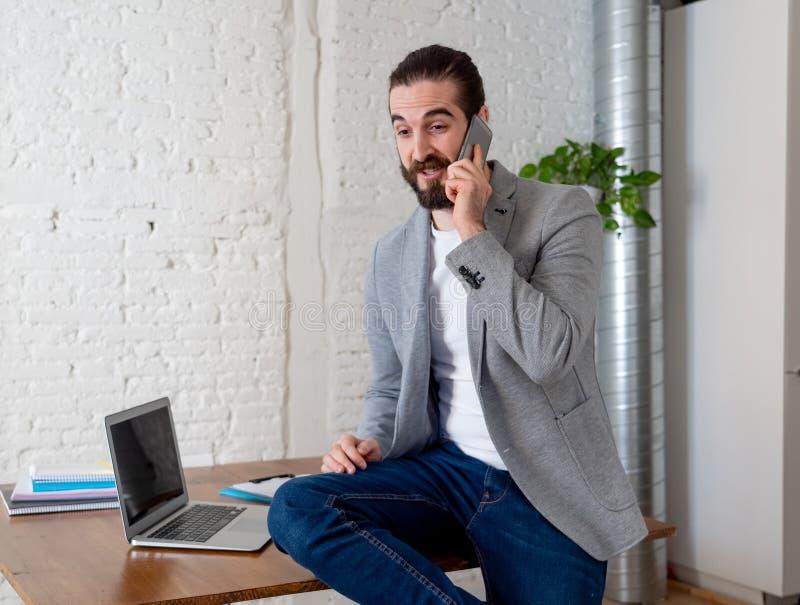 Portret van jonge gelukkige aantrekkelijke sprekende zaken van de ondernemersmens op mobiel stock afbeelding