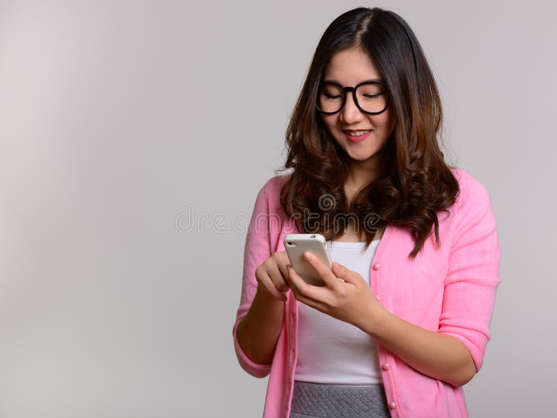 Portret van jonge gelukkige Aziatische vrouw die mobiele telefoon met behulp van royalty-vrije stock foto's