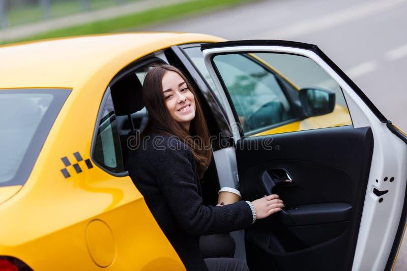 Portret van jonge gelukkige donkerbruine vrouwenzitting in taxi stock foto's