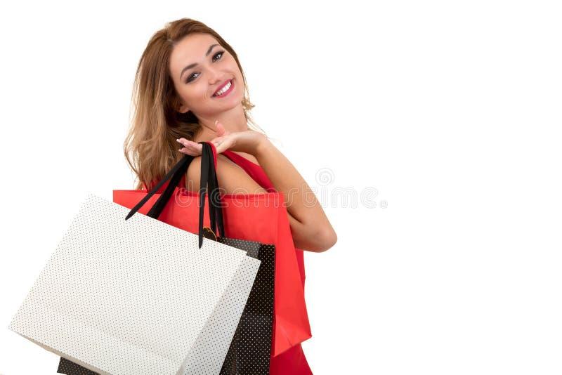 Portret van jonge gelukkige glimlachende die vrouw met het winkelen zakken, over witte achtergrond wordt geïsoleerd royalty-vrije stock afbeeldingen