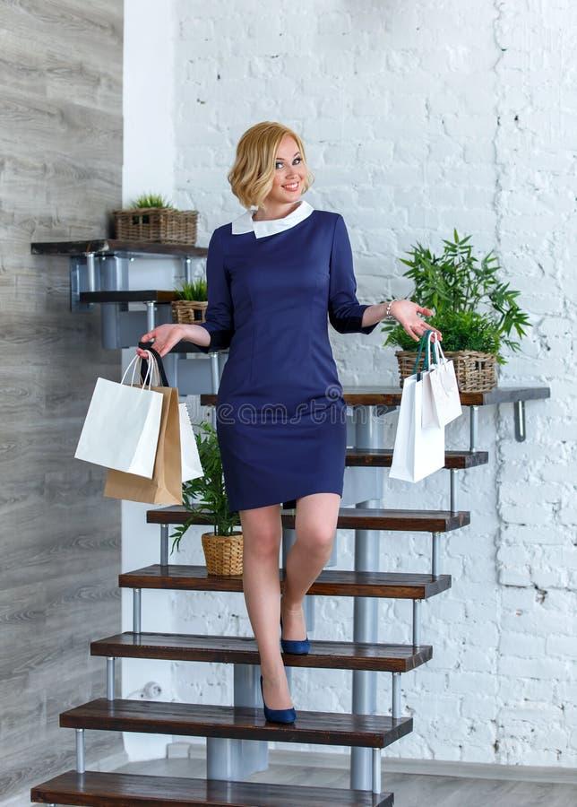 Portret van jonge gelukkige glimlachende vrouw met het winkelen zakken royalty-vrije stock afbeelding
