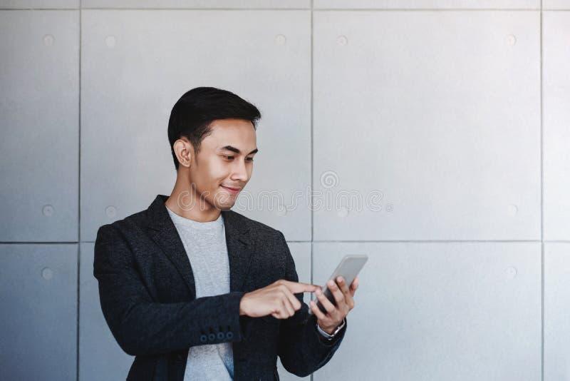 Portret van Jonge Gelukkige Zakenman Using Smartphone Status door de Industriële Concrete Muur Lezingsbericht via Mobiele Telefoo stock foto