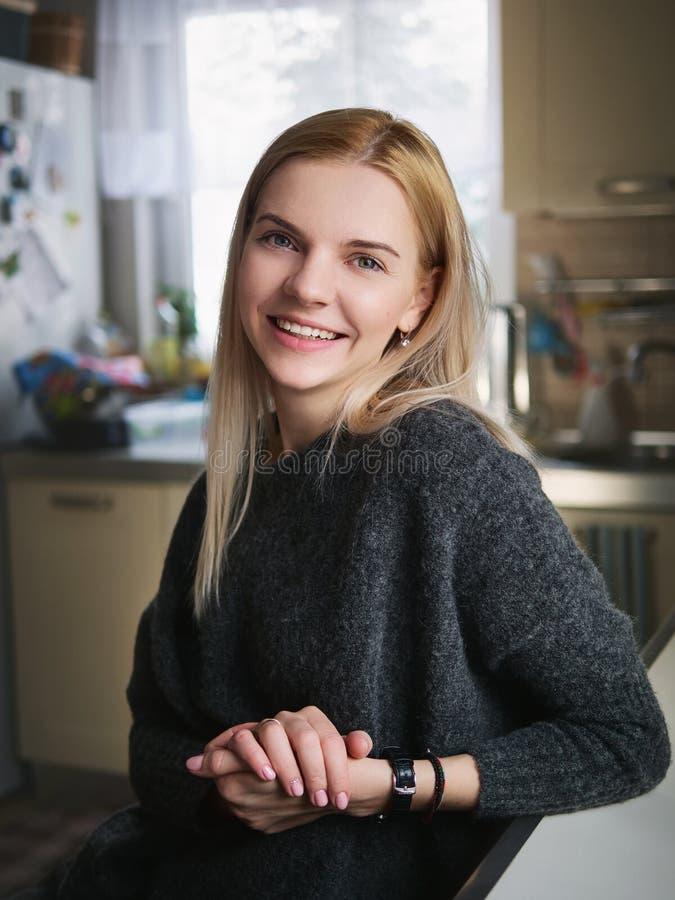 Portret van jonge glimlachende aanbiddelijke blonde Europese vrouw die ogenblik van het stellen genieten tegen vaag binnenlandse  royalty-vrije stock afbeeldingen