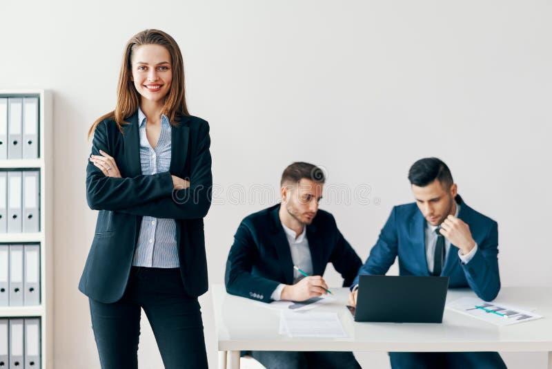 Portret van jonge glimlachende bedrijfsvrouw met gekruiste wapens en haar commercieel team op achtergrond royalty-vrije stock afbeelding