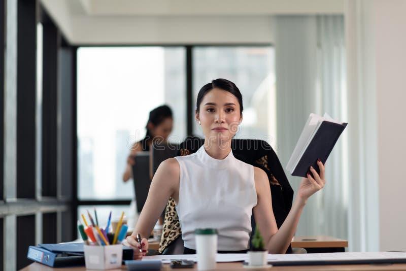 Portret van jonge glimlachende onderneemster die in het bureau werken royalty-vrije stock foto