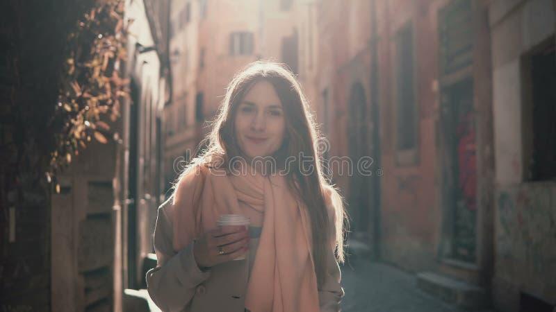 Portret van jonge glimlachende vrouw die camera bekijken Gelukkig aantrekkelijk meisje die zich in ochtendstraat bevinden, die om royalty-vrije stock afbeelding