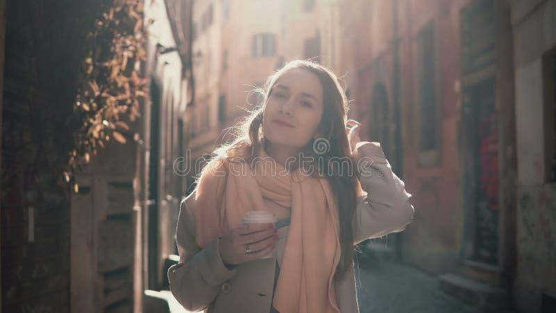 Portret van jonge glimlachende vrouw die camera bekijken Gelukkig aantrekkelijk meisje die zich in ochtendstraat bevinden, die om royalty-vrije stock afbeeldingen