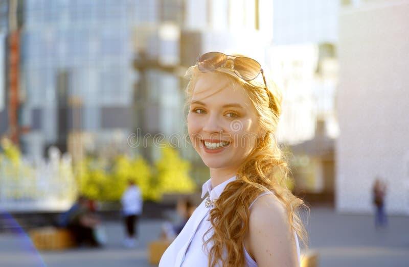 Portret van jonge glimlachende vrouw die zonnebril omhoog op hoofd dragen die camera bekijken stock foto's
