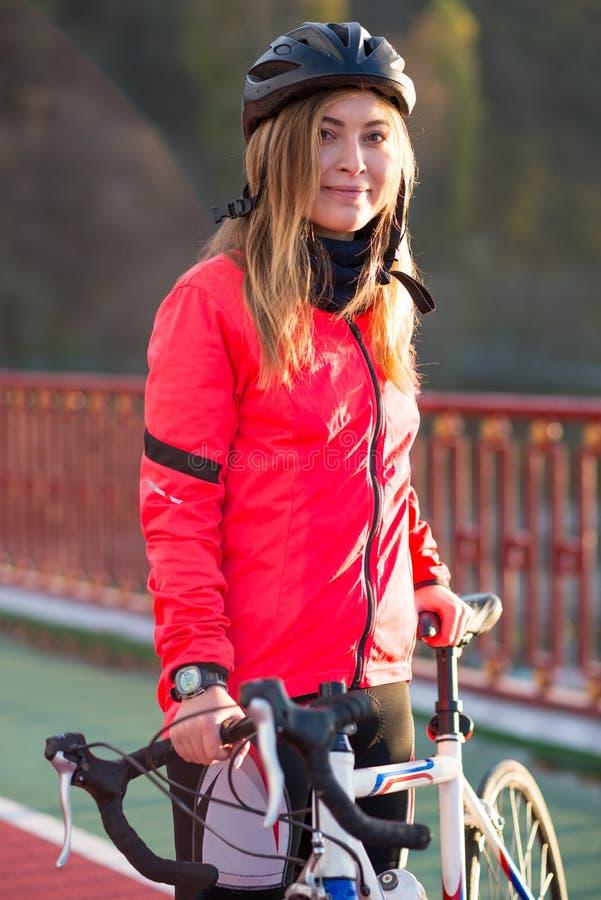 Portret van Jonge Glimlachende Vrouwelijke Fietser in Oranje Jasje die met Wegfiets rusten in Koud Sunny Autumn Day royalty-vrije stock afbeelding