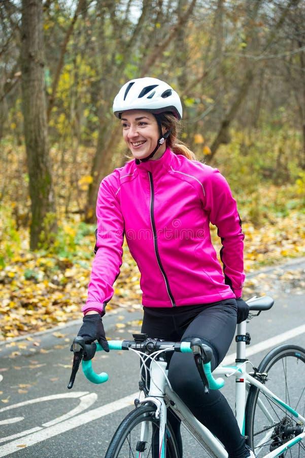Portret van Jonge Glimlachende Vrouwelijke Fietser in Roze Jasje die met Wegfiets rusten in Koud Sunny Autumn Day royalty-vrije stock afbeelding