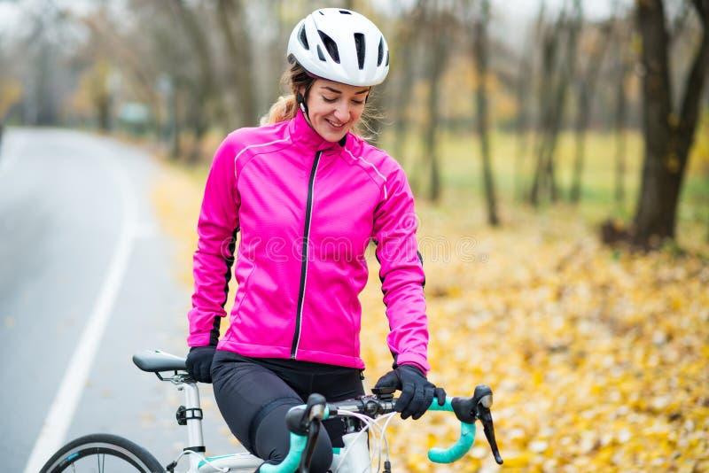 Portret van Jonge Glimlachende Vrouwelijke Fietser in Roze Jasje die met Wegfiets rusten in Koud Sunny Autumn Day stock afbeelding