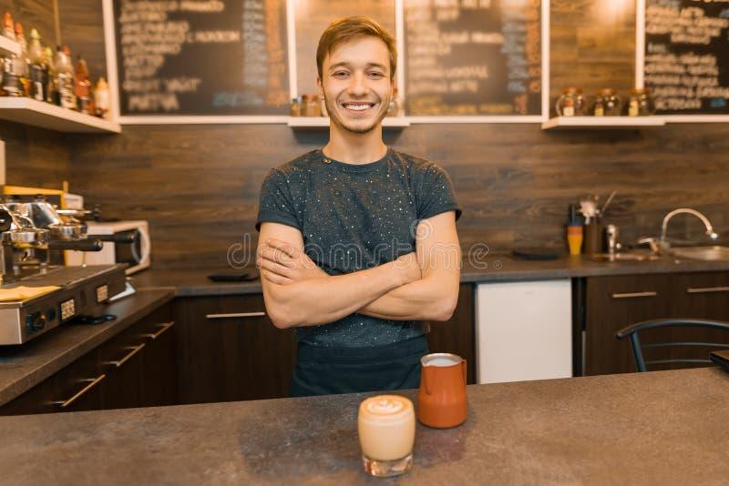 Portret van jonge het glimlachen mannelijke barista met voorbereide die drank met wapens status achter koffieteller worden gekrui stock foto