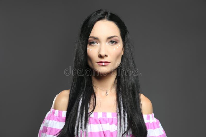 Portret van jonge hippievrouw met bohomake-up in modieuze uitrusting op grijze achtergrond royalty-vrije stock afbeeldingen