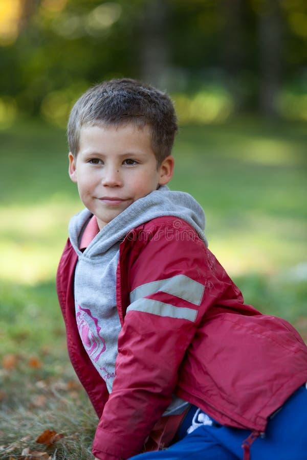 Portret van jonge jongen in rood jasje die op gras leggen stock fotografie
