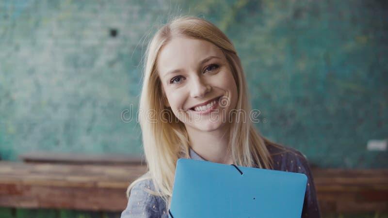 Portret van jonge Kaukasische blondevrouw die camera bekijken en op modern kantoor glimlachen Succesvolle werknemer op het werk royalty-vrije stock afbeelding