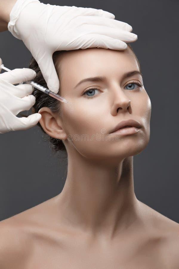 Portret van jonge Kaukasische vrouw die kosmetische injectie krijgen royalty-vrije stock afbeelding