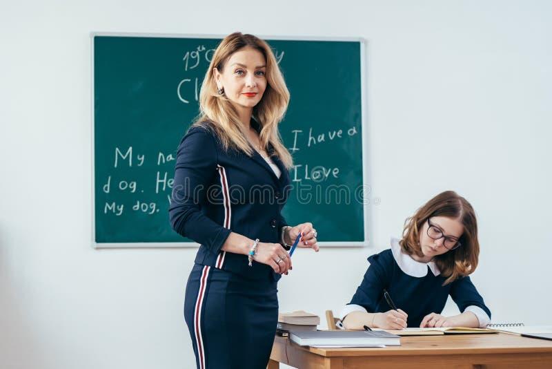 Portret van jonge Kaukasische vrouwelijke leraar in schoolklaslokaal royalty-vrije stock afbeelding