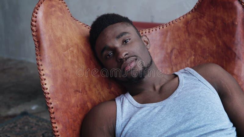 Portret van jonge knappe Afrikaanse mensenzitting op de leerstoel en het bekijken camera Ernstig modelmannetje stock foto's