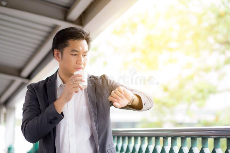 Portret van jonge knappe het bedrijfsmens drinken koffie die polshorloge bekijken royalty-vrije stock foto