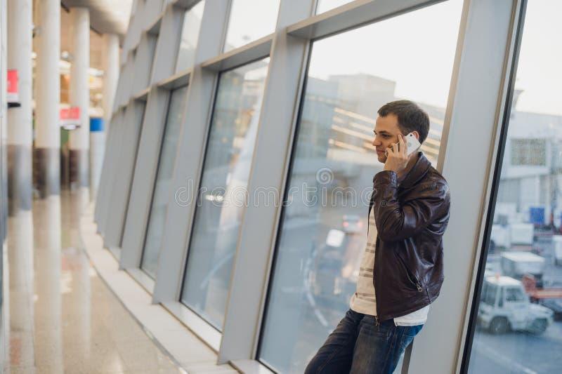 Portret van jonge knappe persoon die toevallige stijlkleren dragen die zich dichtbij venster in moderne luchthaventerminal bevind royalty-vrije stock afbeeldingen