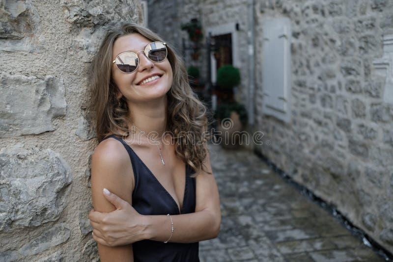 Portret van Jonge krullende blondevrouw in lange kleding en sunglasse stock fotografie