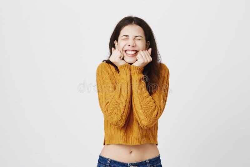 Portret van jonge leuke Europese student die met emoties worden overweldigd, uitdrukkend opwinding en geluk met gesloten stock foto's