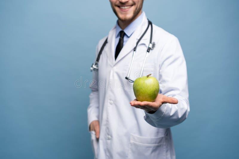 Portret van jonge mannelijke arts die groene appel houden Geïsoleerdt op lichtblauw stock afbeelding