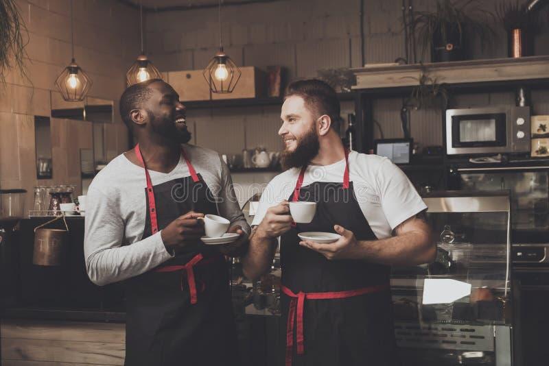 Portret van jonge mannelijke barista twee bij het werkruimte stock foto