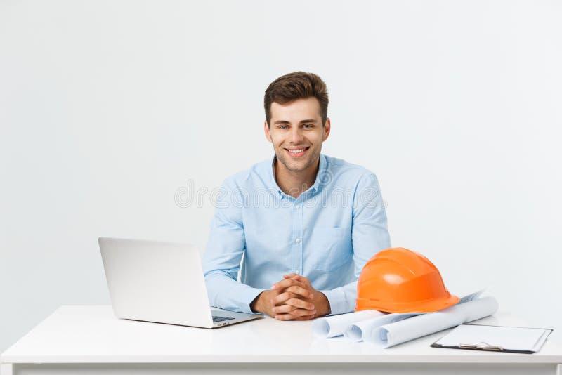 Portret van jonge mannelijke binnenlandse ontwerper of ingenieur die terwijl het zitten op zijn bureaulijst glimlachen royalty-vrije stock foto