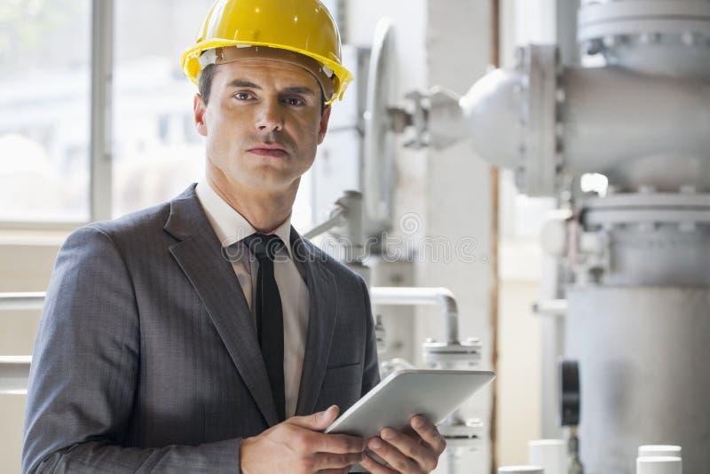 Portret van jonge mannelijke de tabletcomputer van de architectenholding in de industrie stock afbeeldingen