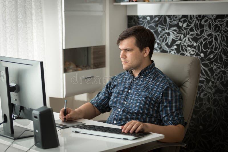 Portret van jonge mannelijke grafische ontwerper die thuis bureau met grafische tablet werken stock fotografie
