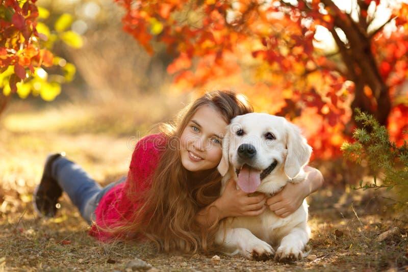 Portret van Jonge meisjeszitting ter plaatse met haar hondretriever in de herfstscène royalty-vrije stock afbeelding