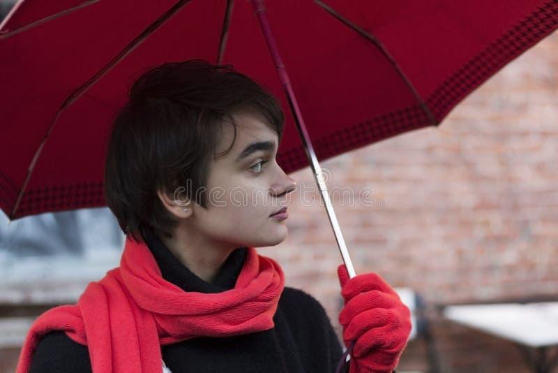 Portret van jonge melancholische vrouw in een rode sjaal onder unmbrella op de regenachtige straat Concept eenzaamheid De ruimte  stock afbeelding