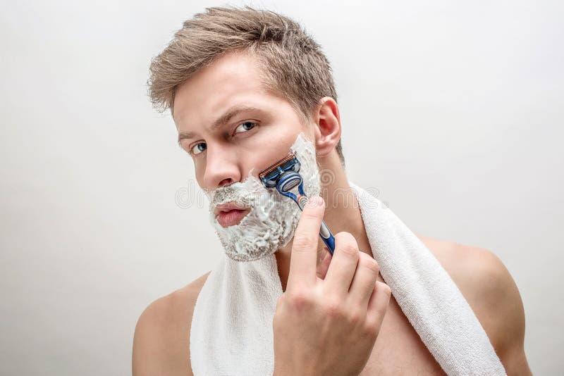 Portret van jonge mens het scheren Hij heeft wit schuim op baard De kerel is ernstig en geconcentreerd Geïsoleerdj op witte achte royalty-vrije stock foto's