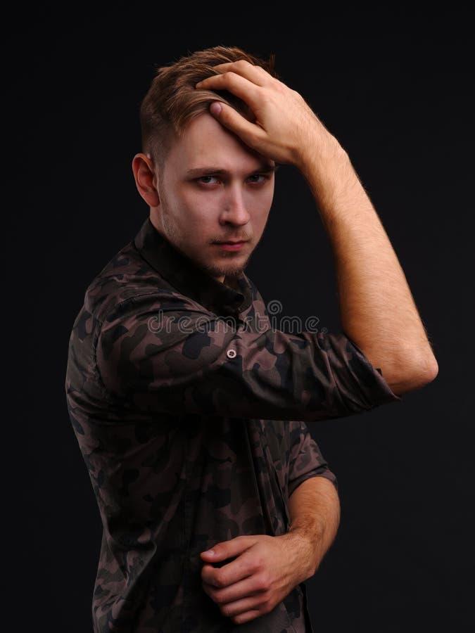 Portret van jonge mens het stellen op een zwarte achtergrond stock afbeeldingen