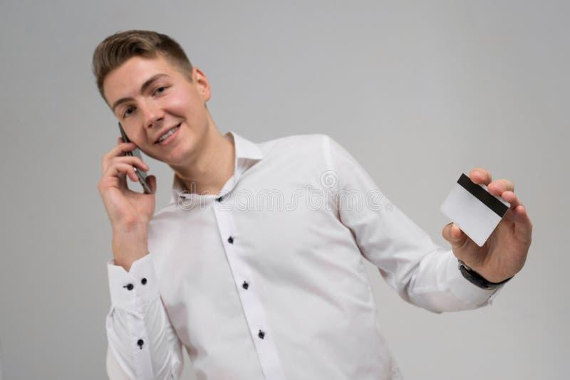 Portret van jonge mens spreken op mobiele telefoon met creditcard ter beschikking geïsoleerd op witte achtergrond royalty-vrije stock foto