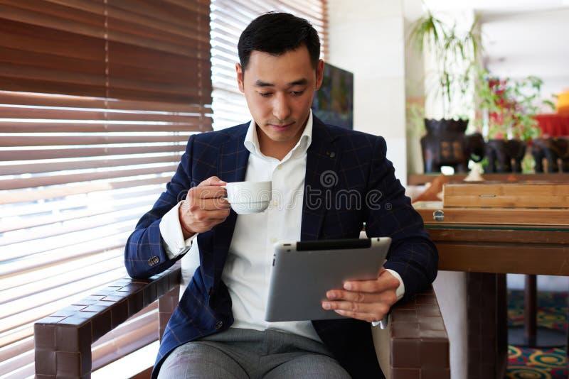Portret van jonge mensenondernemer die in formele slijtage van koffie genieten terwijl het lezen van nieuws op digitale tablet, stock foto
